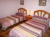 Doble  camas, lampara, mesa, silla, armario y lavabo.