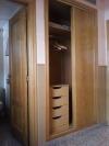 Los armarios son de madera y tienen cajonera y perchas para la ropa